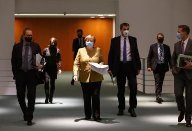 Kanzlerin Angela Merkel (M) schreitet mit Ländervertretern zur Pressekonferenz, um die Corona-Ergebnisse vorzustellen. Foto: Odd Andersen/AFP/POOL/dpa