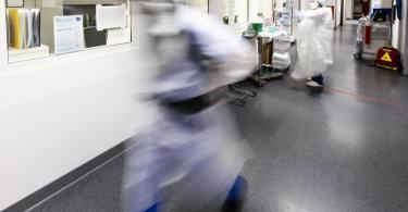 Ein Krankenpfleger läuft über den Flur einer Intensivstation. Foto: Frank Molter/dpa