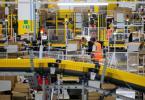 Mitarbeiter mit Mund-Nasen-Bedeckung in einem Logistikzentrum des Versandhändlers Amazon in Mönchengladbach. Foto: Rolf Vennenbernd/dpa