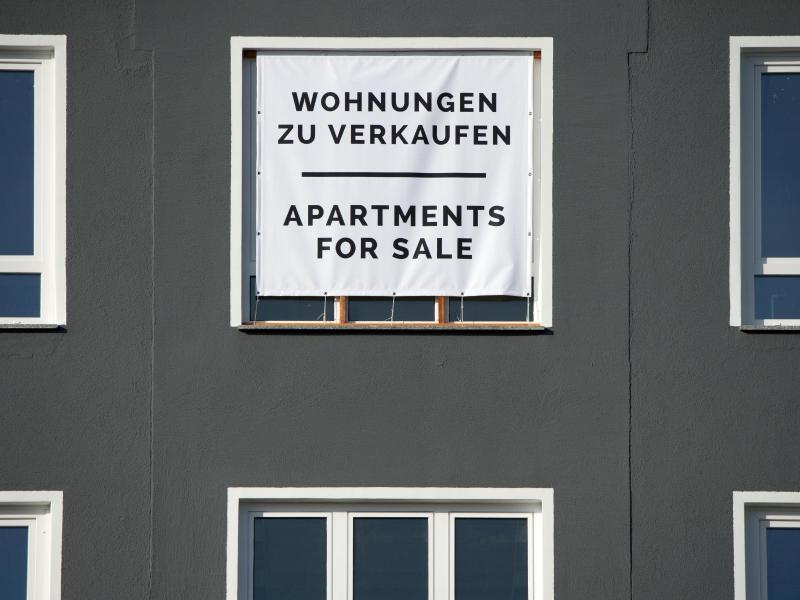 Mit einem großen Plakat werden Wohnungen zum Kauf angeboten. Weniger Maklerkosten entlasten Immobilienkäufer vor allem in Städten, wo Häuser und Wohnungen sehr teuer sind. Foto: Andrea Warnecke/dpa