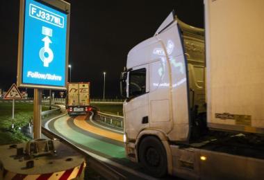 """Ein Lastwagen aus Großbritannien fährt auf dem Weg zum Eurotunnel-Terminal auf einer Straße mit grünen und orangefarbenen Linien, die Teil der neuen """"Smart Border""""-Zollinfrastruktur ist. Foto: Lewis Joly/AP/dpa"""