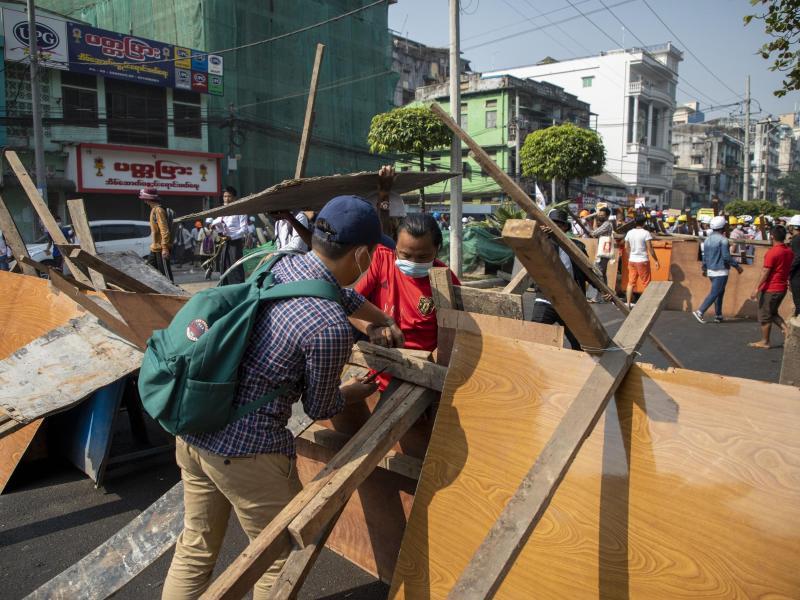 Mit Straßensperren aus Hölzern und Sperrholzplatten wollen die Demonstranten die Polizisten am Vordringen hindern. Foto: Thuya Zaw/ZUMA Wire/dpa
