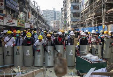 Mit Helmen und Schutzbrillen ausgerüstet schlagen die Demonstranten auf handgefertigte Schilder und bilden eine Schutzwand gegen die Polizei. Foto: Thuya Zaw/ZUMA Wire/dpa