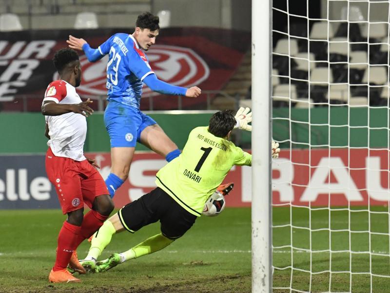Janni Serra (M) von Holstein Kiel erzielt gegen die Essener Daniel Heber (l) und Torwart Daniel Davari das Tor zur 2:0-Führung. Foto: Martin Meissner/AP POOL/dpa