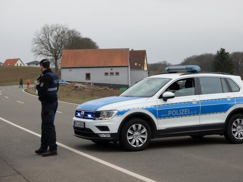 Eine Straße wird mit einem Einsatzfahrzeug der Polizei abgesperrt. Foto: Harald Tittel/dpa