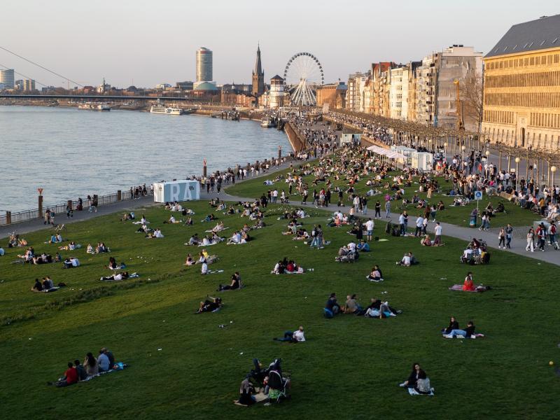 Menschen halten sich an der Rheinuferpromenade und den Rheinwiesen inDüsseldorf auf. Laut dem RKI breitet sich die sehr ansteckende Corona-Variante B.1.1.7 rasch in Deutschland aus. Foto: Jonas Güttler/dpa