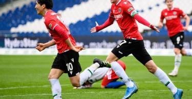 Genki Haraguchi (l) und Marvin Ducksch retteten Hannover 96 noch einen Punkt gegen den HSV. Foto: Swen Pförtner/dpa-POOL/dpa