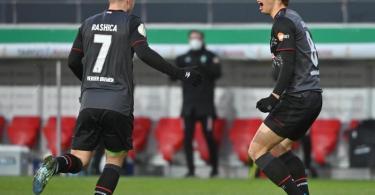 Bremens Torschütze Yuya Osako feiert mit Milot Rashica (l) das Tor zum 1:0 gegen Jahn Regensburg. Foto: Armin Weigel/dpa