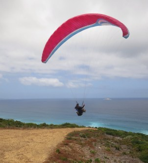Paraglider making a perfect takeoff above the beach
