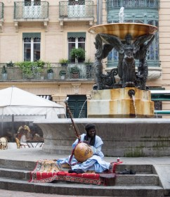 Many North Africans in the city. This guy busking contrasts with the old fountain