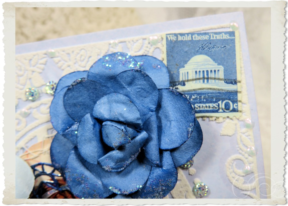 Details of USA postal stamp in blue and  a rose on handmade card