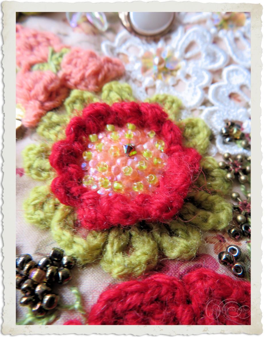 Handmade red green crochet flower with beaded heart