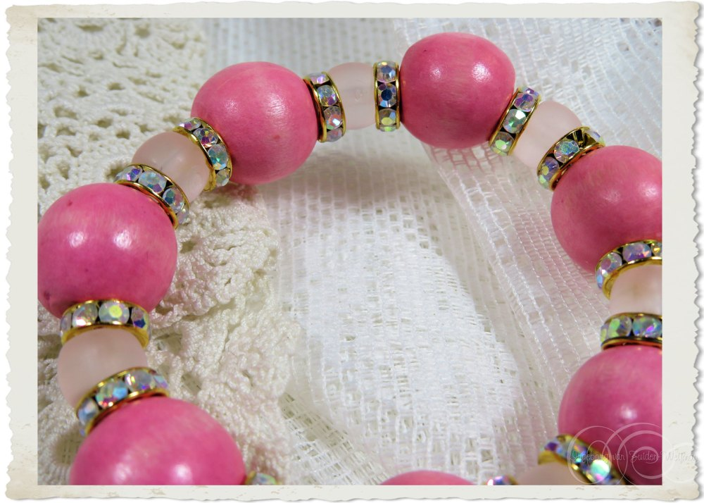 Details of handmade pink ball bracelet with strass rondelles