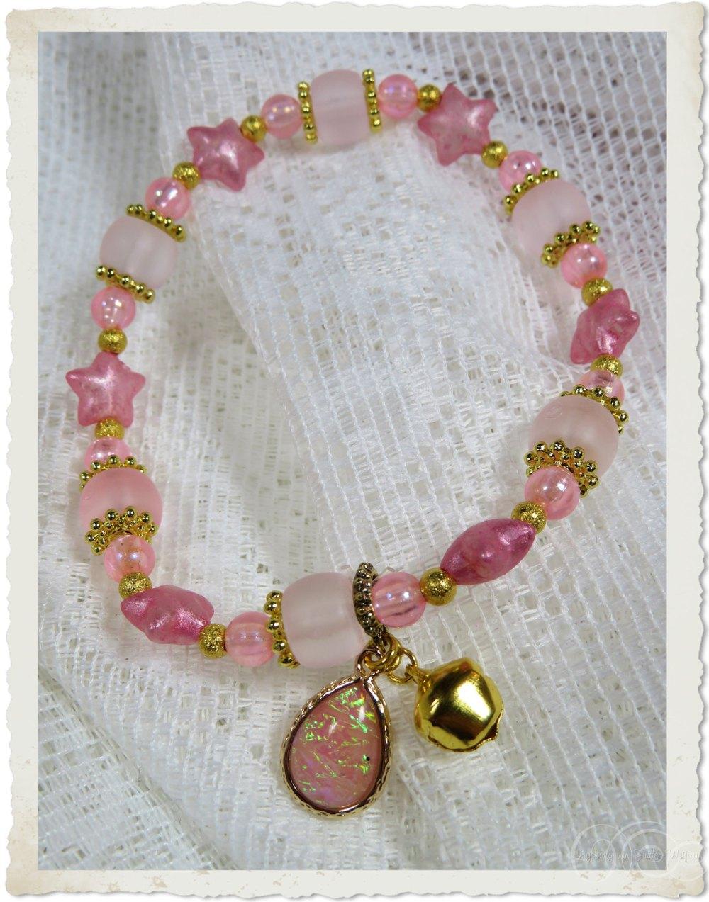 Pink bracelet with stars and bell by Ingeborg van Zuiden