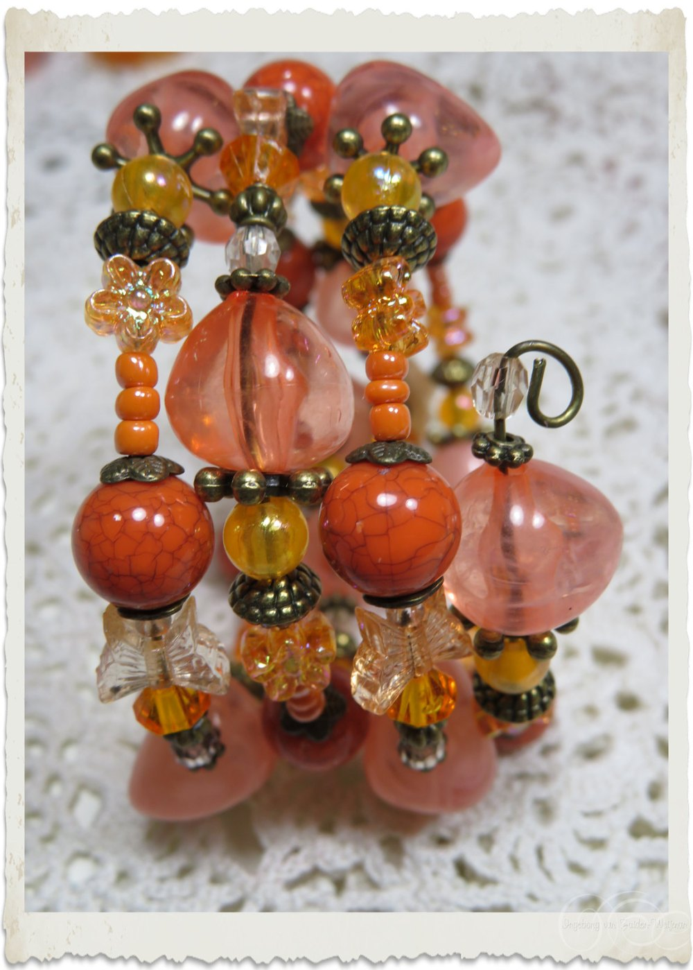 Orange beads on handmade bracelet by Ingeborg
