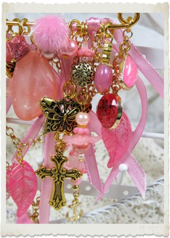 Details of pink gold brooch with charms and dangles