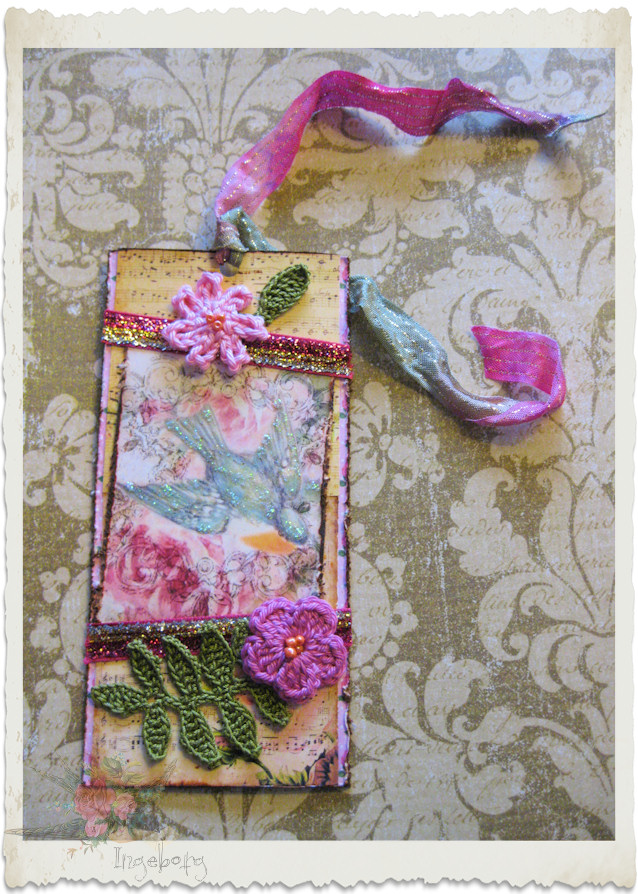 Details of pink handmade tag with crochet florals