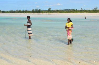 Landsby koner på vej hjem med dagens fangst fra Murrebue beach