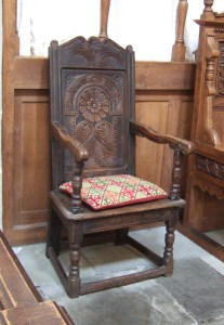 A beautiful Jacobean carved oak chair near the altar.