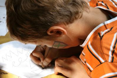 Jongen die aan het oefenen is met schrijfbewegingen.