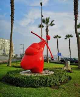 statua rossa in un parco di palme