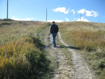 A man in a dark jacket and faded blue jeans walks up a dirt path toward an amazingly blue sky with fluffy white clouds (Nose Hill, Calgary, Alberta, Canada)
