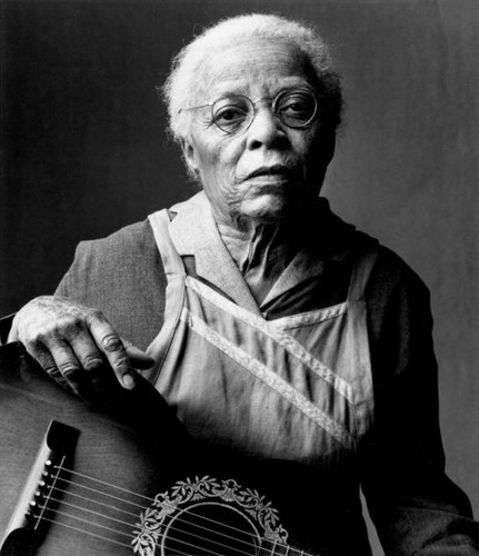 "Actress Ruby Dee in costume as Mother Abigail in the 1994 mini-series ""The Stand"". A black and white photo of an elderly black woman in a modest dress and cotton apron. She is seated with an acoustic guitar on her lap."