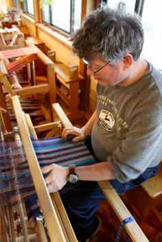 Mitch works independently at his loom to create hand-woven placemats