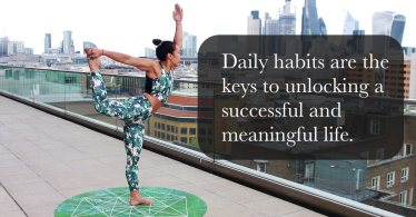 A lady in performing yoga on a roof of a building outline in a city scape. A caption reads, Daily habits are the keys to unlocking a successful and meaningful life.