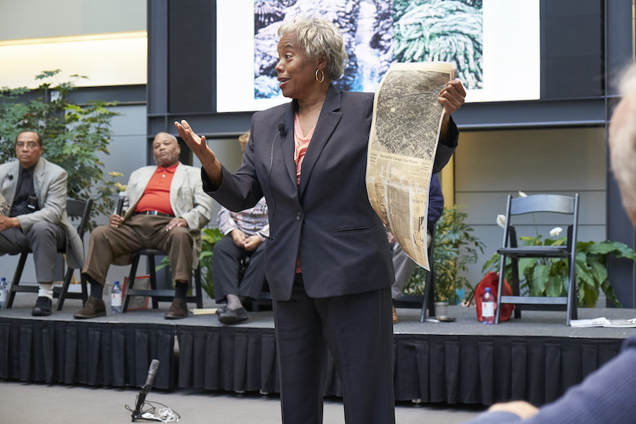 Woman sharing old newspaper article during a neighborhood forum.