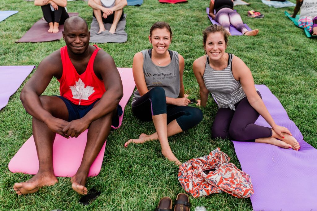 People practice yoga at Bailey Park during Sunset Salutations community event.
