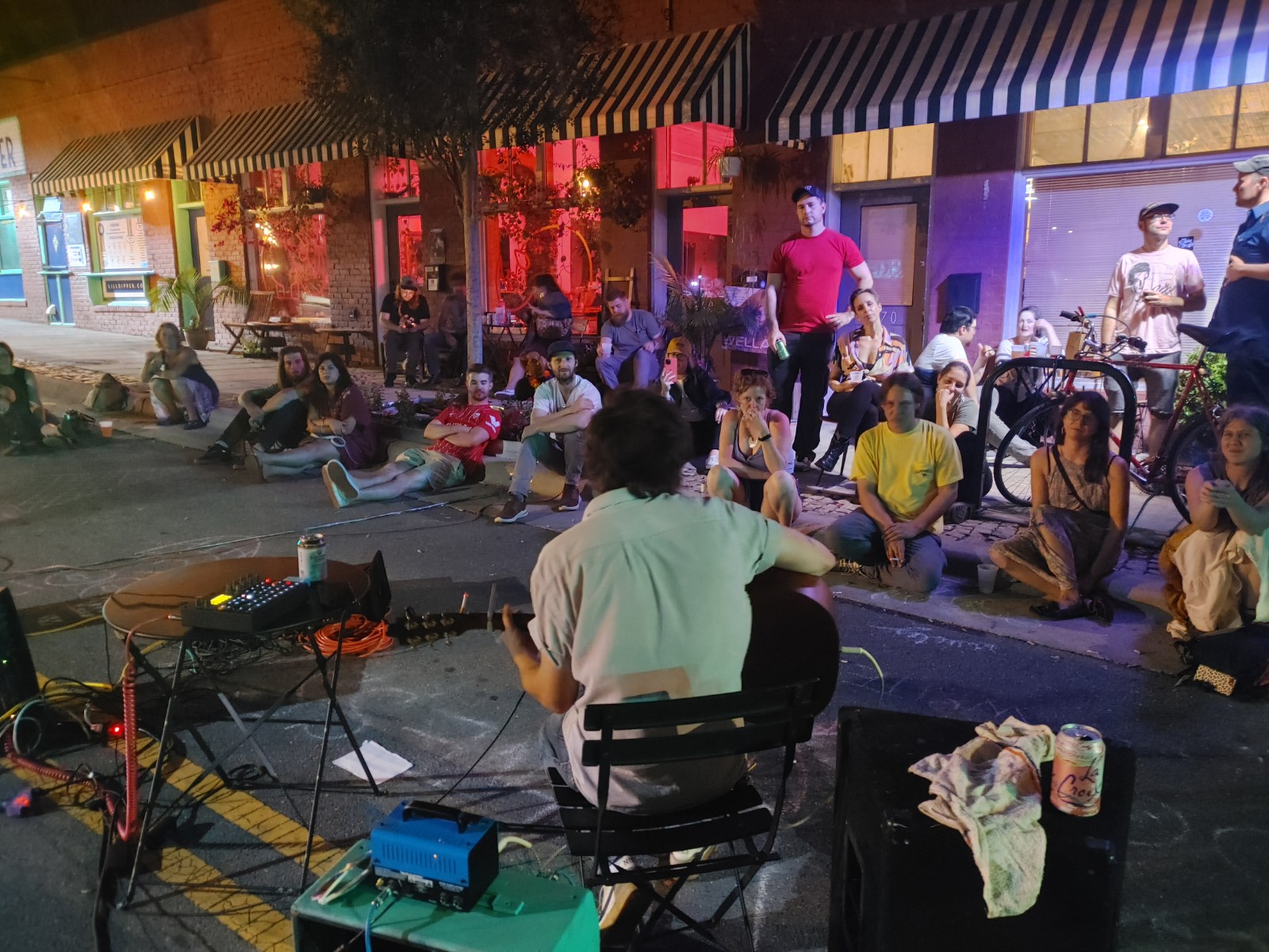 Man playing guitar at night with crowd listening to his music on sidewalk outside of Fair Witness.