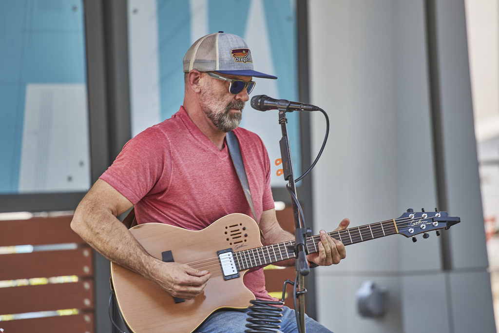 Man plays guitar on stage at Bailey Park during Food Truck Friday.