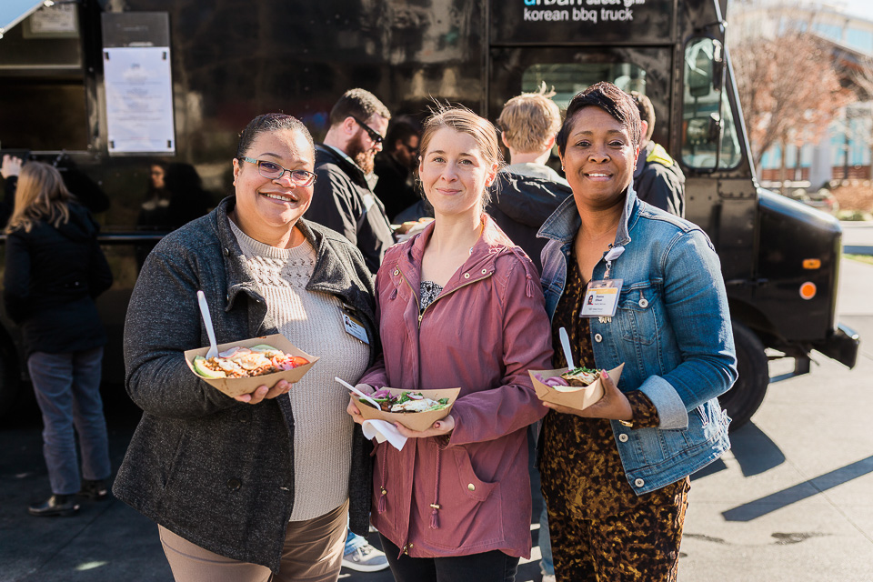 Three women pose for photograph during Food Truck Friday.