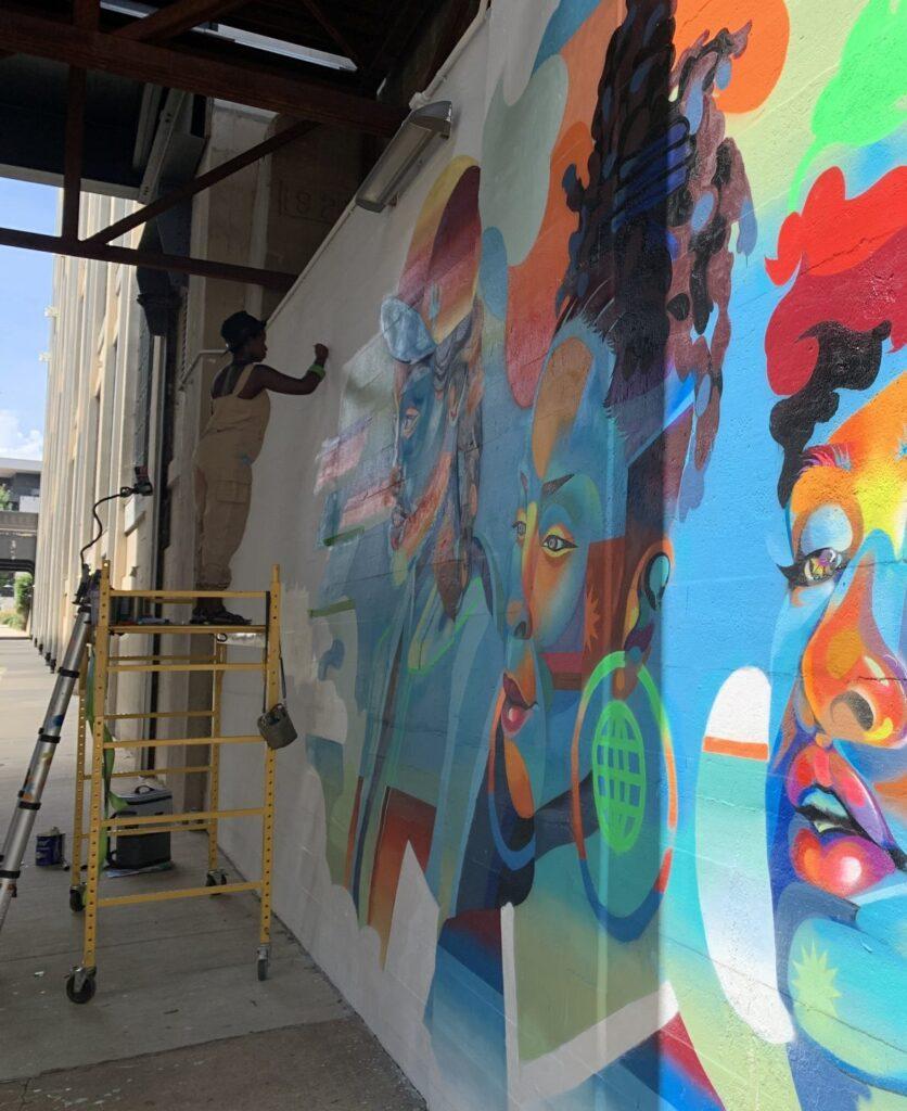 Georgie Nakima works on mural.