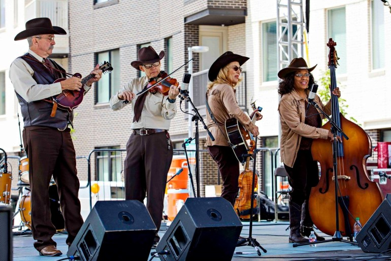 four musicians in cowboy hats playing instruments on stage at the Festival of the Arts in downtown Oklahoma City