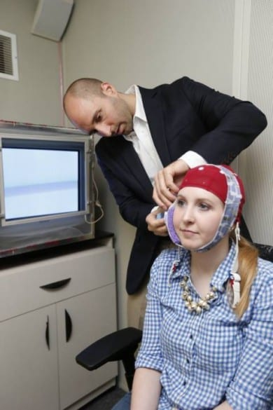 Robert Reinhart applies the electrical stimulus to subject Laura McClenahan. After 20 minutes the headband is removed and the EEG cap will capture readings of her brain as she executes the learning task. (John Russell / Vanderbilt University)