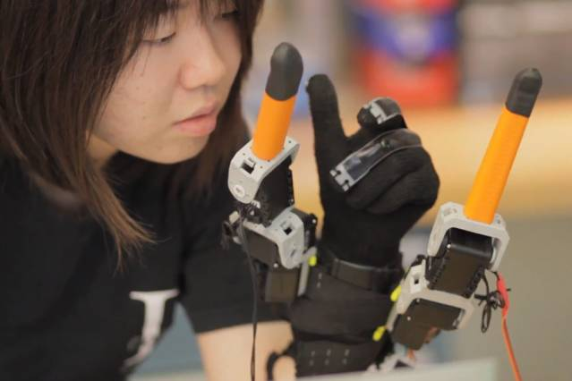 "Faye Wu, a graduate student in mechanical engineering, demonstrates the ""supernumerary robotic fingers"" device Photo: Melanie Gonick/MIT"