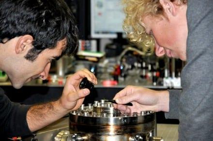 PhD students Giovanni Guccione (L) and Harry Slatyer examine their gold-coated silver gallium nanowire in the Quantum Optics labs. Image: Quantum Optics Group, ANU