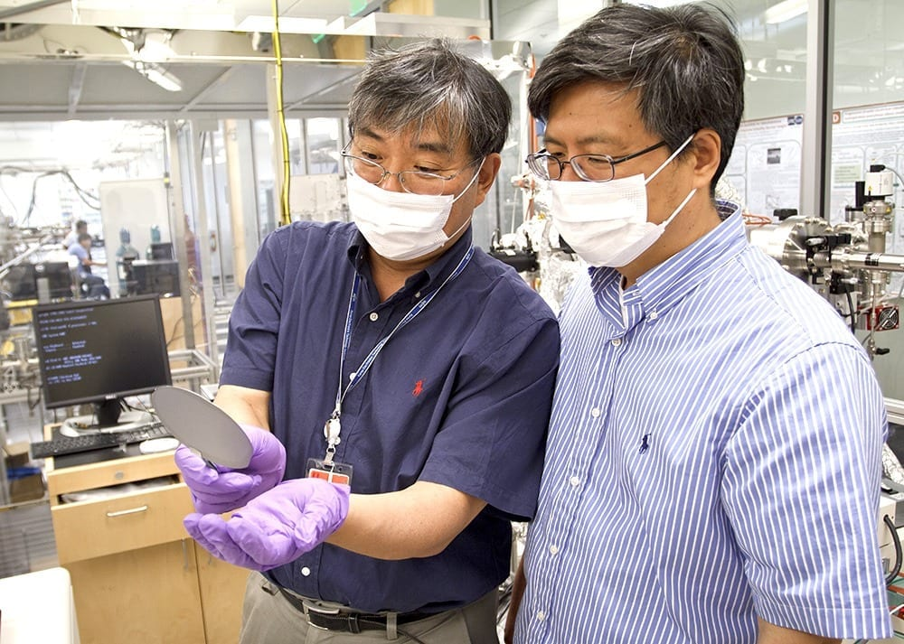 "Dr. Jiyoung Kim (left) and Dr. Kyeongjae ""K.J."" Cho examine a wafer used to make transistors. The two created new technology that could reduce energy consumption in mobile devices and computers."