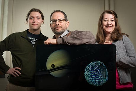 Jason Koski/University Photography Graduate student James Stevenson, astronomer Jonathan Lunine and chemical engineer Paulette Clancy, with a Cassini image of Titan in the foreground of Saturn, and an azotosome, the theorized cell membrane on Titan.