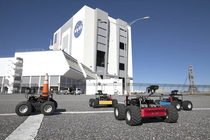 """The four robotic """"Swarmies"""" begin a test run at NASA's Kennedy Space Center in Florida. The robots are autonomous and programmed to use random search methods to find resources. Image Credit: NASA/Dmitri Gerondidakis"""