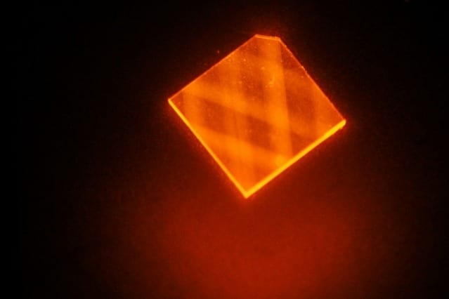 """In this image, laser light enters a synthetic diamond from a facet at its corner and bounces around inside the diamond until its energy is exhausted. This excites """"nitrogen vacancies"""" that can be used to measure magnetic fields. image: H. Clevenson/MIT Lincoln Laboratory"""