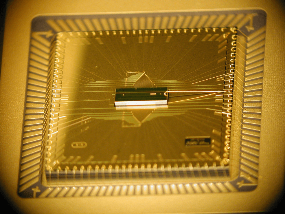 A photograph of the completed BGA trap assembly. The trap chip is at the center, sitting atop the larger interposer chip that fans out the wiring. The trap chip surface area is 1mm x 3mm, while the interposer is roughly 1 cm square. CREDIT: D. Youngner, Honeywell