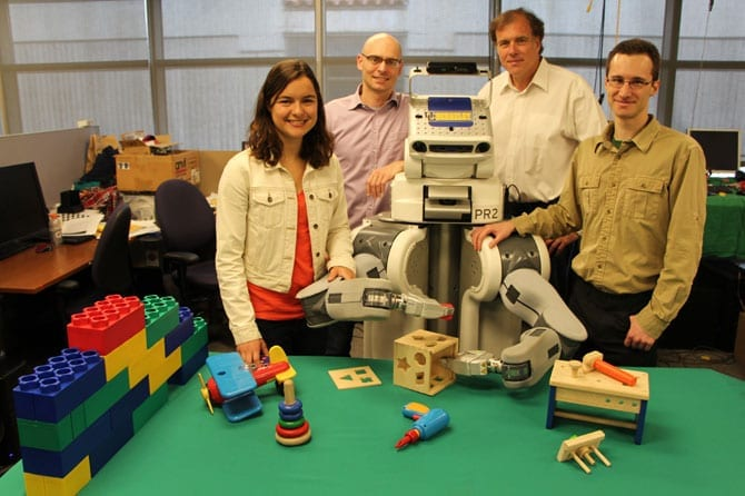This team of UC Berkeley researchers has developed algorithms that enable their PR2 robot, nicknamed BRETT for Berkeley Robot for the Elimination of Tedious Tasks, to learn new tasks through trial and error. Shown, left to right, are Chelsea Finn, Pieter Abbeel, BRETT, Trevor Darrell and Sergey Levine. (Photo courtesy of UC Berkeley Robot Learning Lab)