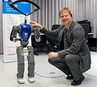"""The small humanoid robot COMAN still has some """"growing"""" to do before it can interact """"eye to eye"""" with human adults. Professor Dr. Jochen Steil is leading the new research project. Photo: Bielefeld University."""