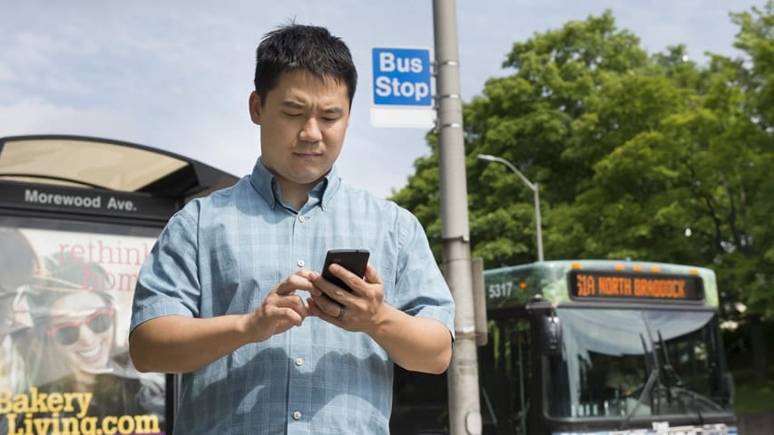 Ph.D. student Adrian deFreitas uses Impromptu, a system that accesses shared apps only when needed, such as a public transit app when the user is standing near a bus stop.