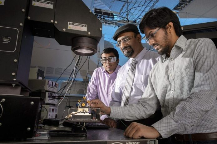 "Doctoral student Aditya G. Baradwaj (at left), professor Muhammad A. Alam (center) and doctoral student Ryyan Khan, operate a solar simulator. They are members of a research team led by former doctoral student Biswajit Ray and also involving assistant professor Bryan Boudouris. The group is reporting new findings that contradict a fundamental assumption about the functioning of ""organic"" solar cells made of low-cost plastics. The findings suggest a new strategy for creating inexpensive solar technology. (Purdue University image/John Underwood)"