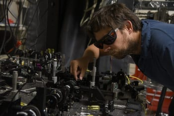 """NIST physicist Krister Shalm with the photon source used in the """"Bell test"""" that strongly supported a key prediction of quantum mechanics: There are in fact """"spooky actions at a distance."""" Photo Credit: Burrus/NIST"""