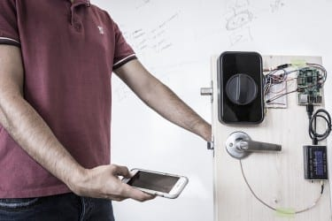 "UW engineers use a smartphone to send a secure password through the human body and open a door with an electronic smart lock. These ""on body"" transmissions employ low-frequency signals generated by the phone's fingerprint sensor.Mark Stone/University of Washington"